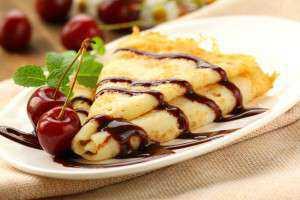 Sweet pancake with chocolate sauce and cherries